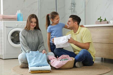 Happy family with clean laundry in bathroom Archivio Fotografico - 140897969