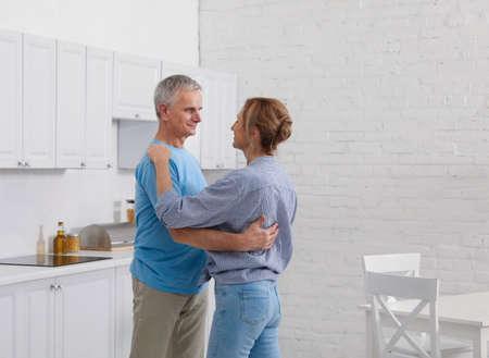 Happy senior couple dancing together in kitchen Foto de archivo - 140897977