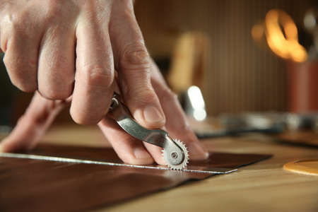 Man marking leather with roller in workshop, closeup