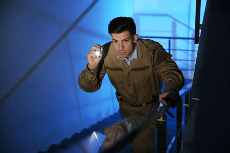 Professional security guard with flashlight on stairs in dark room