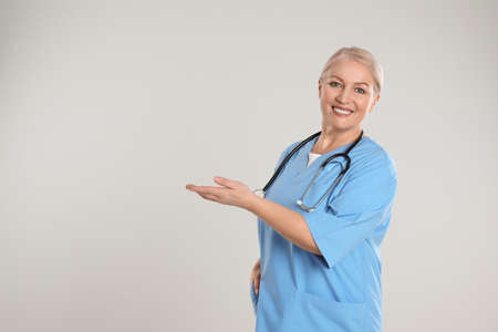 Portrait of mature doctor with stethoscope on light grey background. Space for text Reklamní fotografie