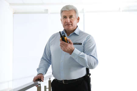 Professional security guard with portable radio set indoors