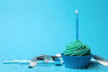 Delicious birthday cupcake with turquoise cream and burning candle on light blue background. Space for text 스톡 콘텐츠