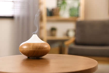 Aroma oil diffuser on wooden table at home, space for text.