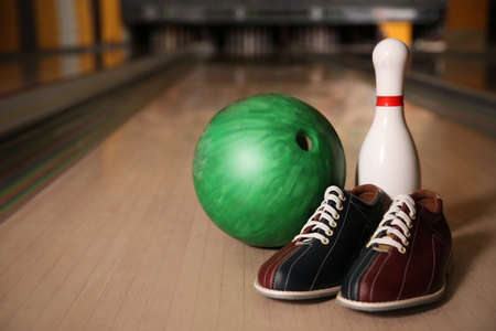 Pin, shoes and ball on alley in bowling club. Space for text 版權商用圖片