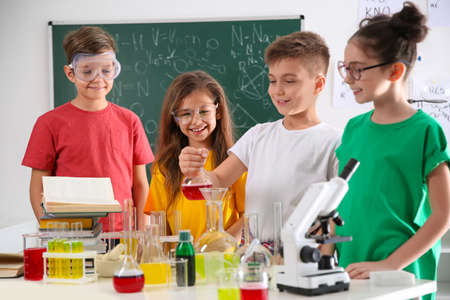 Smart pupils making experiment in chemistry class 免版税图像