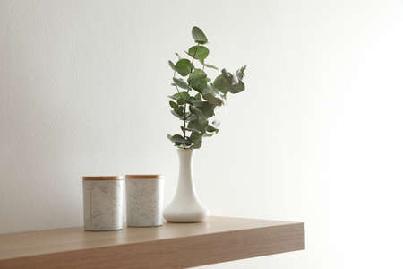 Wooden shelf with decorative elements on light wall Zdjęcie Seryjne