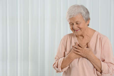 Grateful senior woman with hands on chest against light background. Space for text