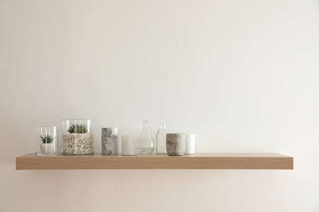 Wooden shelf with plants and decorative elements on light wall Zdjęcie Seryjne