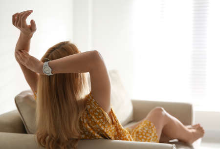 Young woman relaxing on couch near window at home