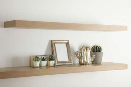 Wooden shelves with photo frame and decorative elements on light wall