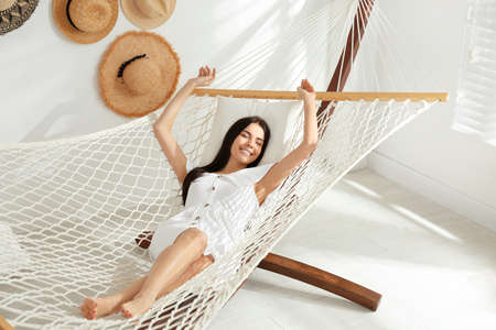 Young woman relaxing in hammock at home Stock Photo