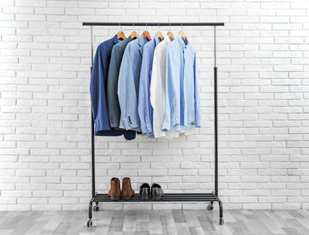 Rack with stylish men's clothes near white brick wall. Space for text