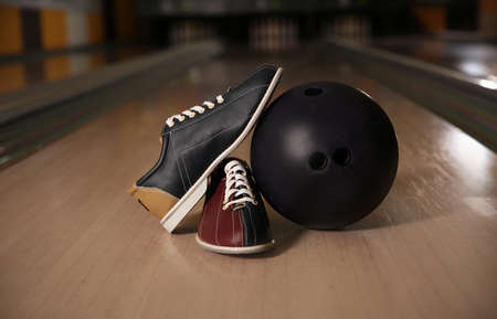 Shoes and ball on bowling lane in club