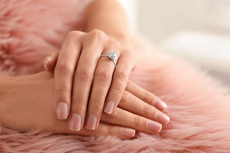 Young woman wearing beautiful engagement ring on faux fur rug, closeup