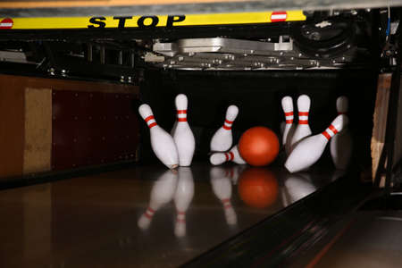 Ball hitting pins on alley in bowling club