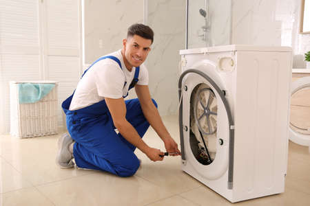 Professional plumber repairing washing machine in bathroom