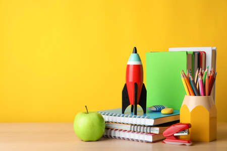 Bright toy rocket and school supplies on wooden table. Space for text