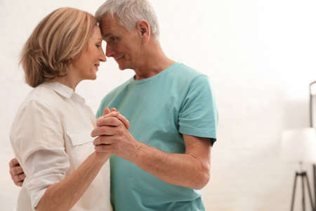 Happy senior couple dancing at home, focus on hands