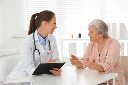 Doctor examining senior patient in modern office Banco de Imagens