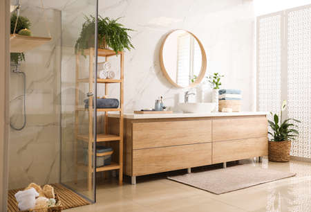 Stylish bathroom interior with countertop, mirror and shower stall. Design idea