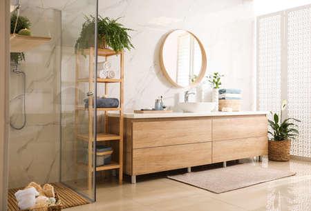 Stylowe wnętrze łazienki z blatem, lustrem i kabiną prysznicową. Pomysł na projekt