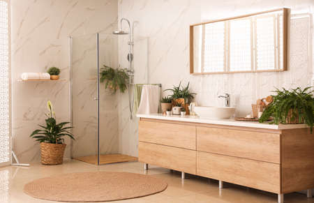 Stylish bathroom interior with countertop, shower stall and houseplants. Design idea