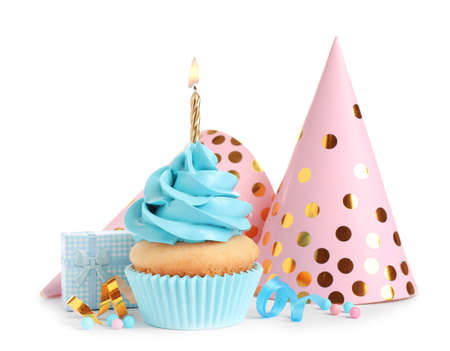 Delicious birthday cupcake with candle, gift and party caps on white background