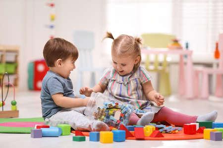 Petits enfants mignons jouant ensemble sur le sol à la maison