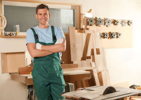 Professional carpenter in uniform near wooden workbench