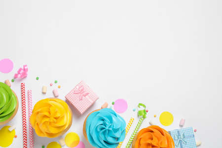 Flat lay composition with colorful birthday cupcakes on white background. Space for text