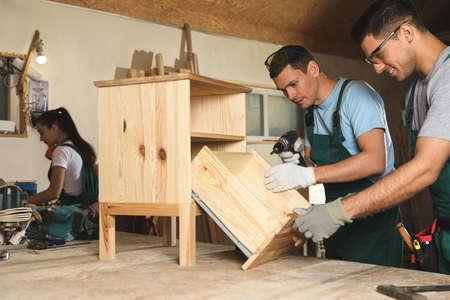 Professional carpenters assembling wooden cabinet in workshop