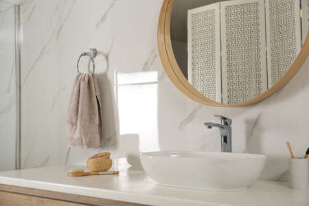 Bathroom interior with mirror, countertop and soft towel on wall