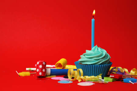 Delicious birthday cupcake with turquoise cream and burning candle on red background. Space for text