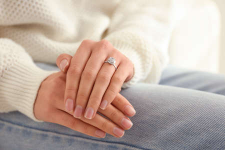 Young woman wearing beautiful engagement ring, closeup