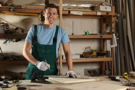 Professional carpenter measuring wooden board in workshop Stockfoto