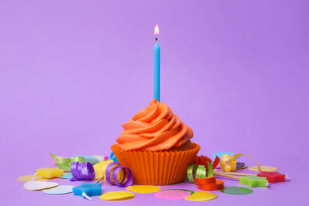Delicious birthday cupcake with orange cream and burning candle on violet background 스톡 콘텐츠