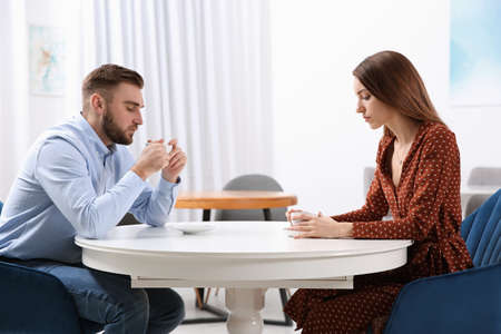 Couple with relationship problems at table in cafe Foto de archivo