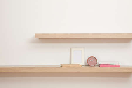 Wooden shelves with books, photo frame and clock on light wall