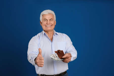 Happy senior man with cash money and wallet on blue background