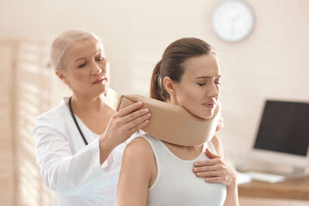 Female orthopedist applying cervical collar onto patient's neck in clinic