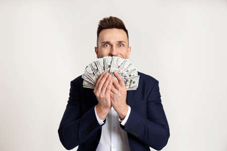 Happy man with cash money on light grey background