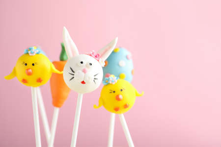 Delicious sweet cake pops on light pink background. Easter holiday
