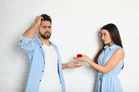 Young woman with engagement ring making marriage proposal to her boyfriend near white brick wall