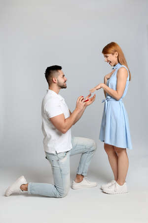 Man with engagement ring making marriage proposal to girlfriend on light grey background