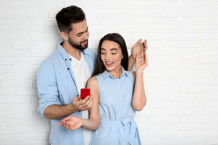 Man with engagement ring making marriage proposal to girlfriend near white brick wall Banco de Imagens