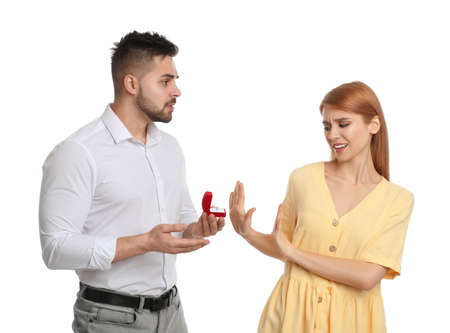Young woman rejecting engagement ring from boyfriend on white background