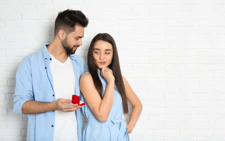Man with engagement ring making marriage proposal to girlfriend near white brick wall