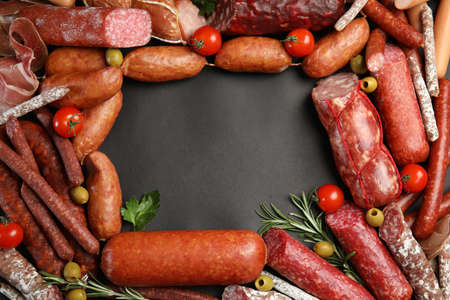 Frame made of different sausages on black background, flat lay. Space for text