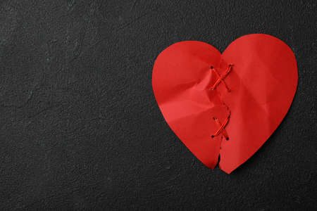 Top view of torn paper heart sewed with thread on black stone background, space for text. Relationship problems concept
